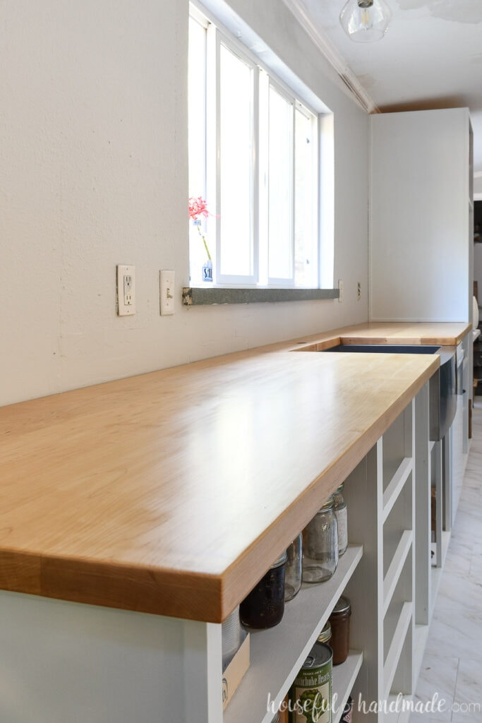 Bank of white cabinets without doors/drawer fronts, sitting in front of a window, with a light wood countertop installed on top.