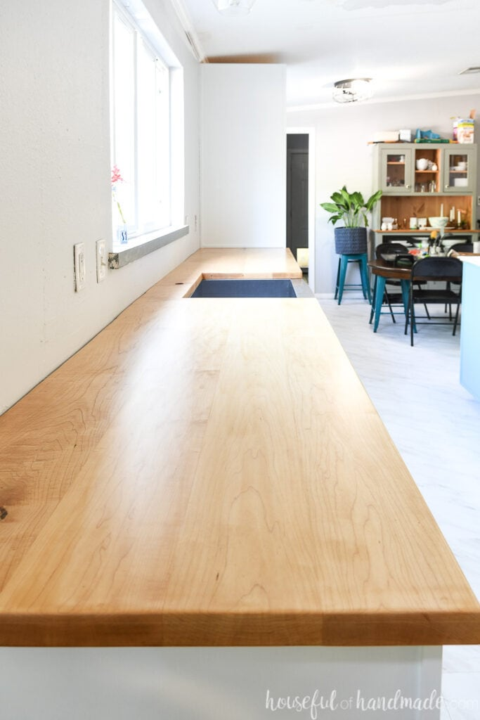 Looking down the length of the long wood countertop in the kitchen with a cut out for a farmhouse sink seeing the dining room in the background.