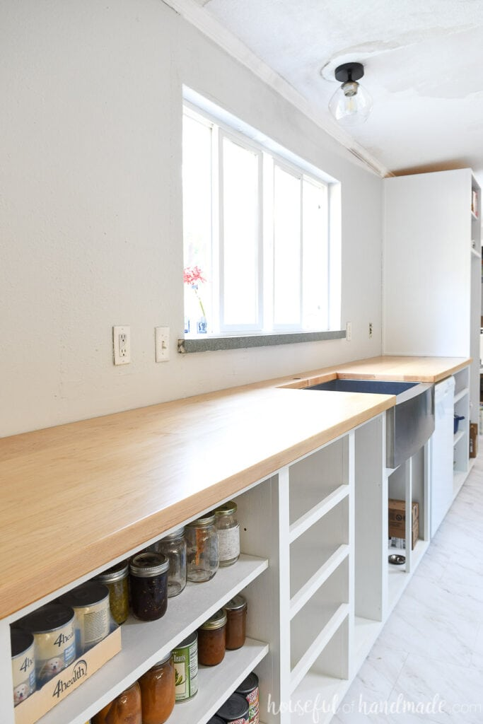 Long wall of base cabinets with a DIY hardwood countertop and stainless steel apron front sink in front of a large window.