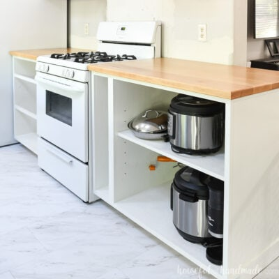 White cabinets around the stove with solid wood countertops sealed with a matte finish on them.