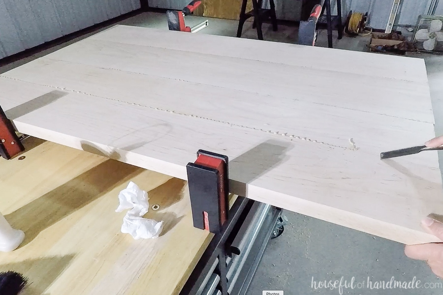 Removing dried glue squeeze out with chisel.