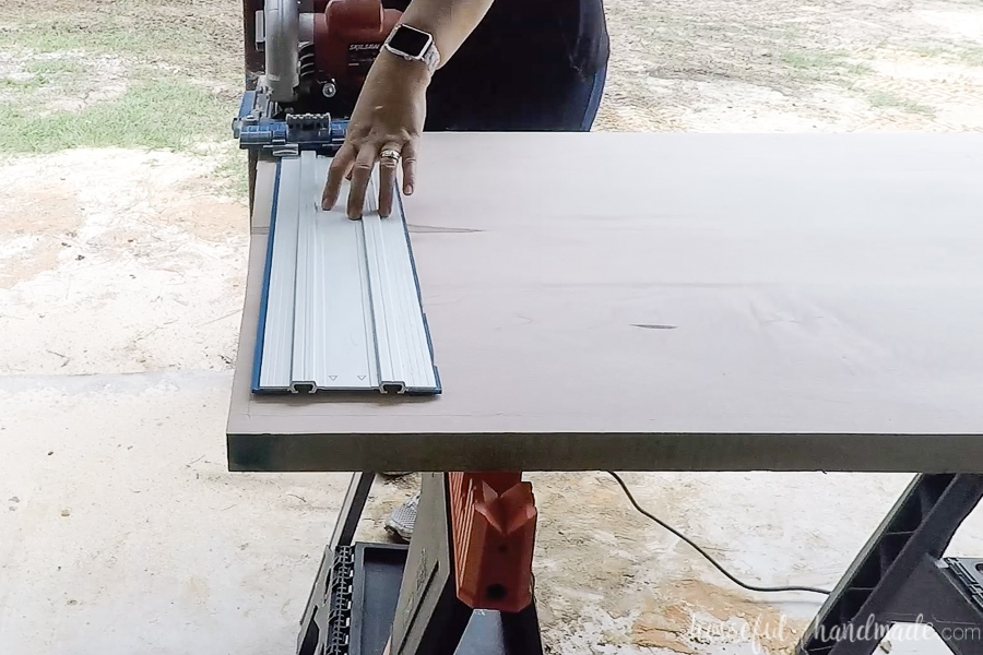 Cutting the edge of the countertop to template with a circular saw and guide track.