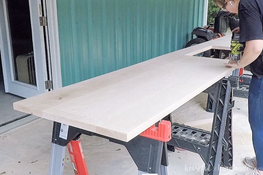 Using a palm router to add a roundover to the top edges of the countertops.