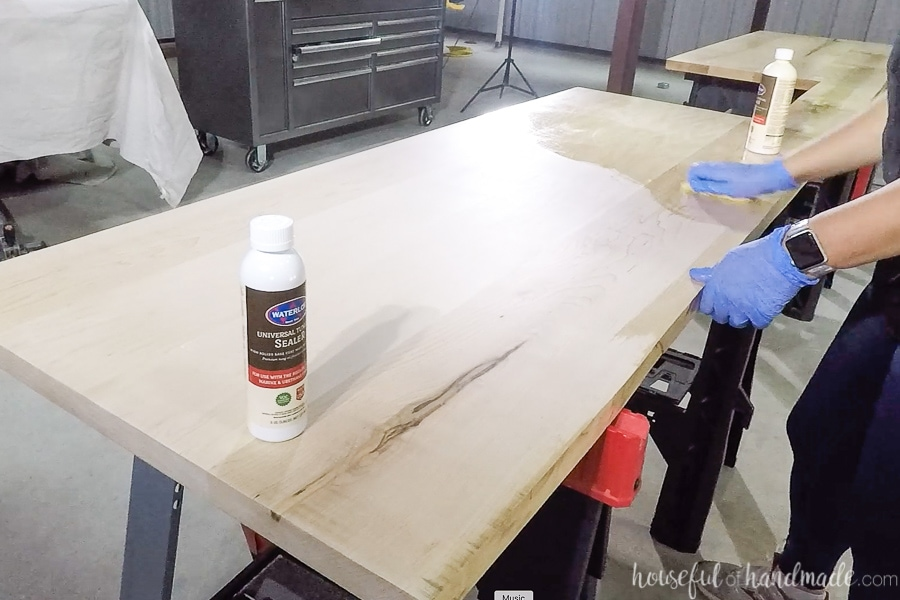 Rubbing the sealer into the wood with a clean rag.