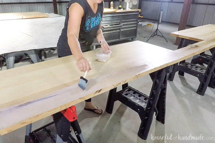 Applying the first coat of waterproof finish to the countertops with a foam brush.
