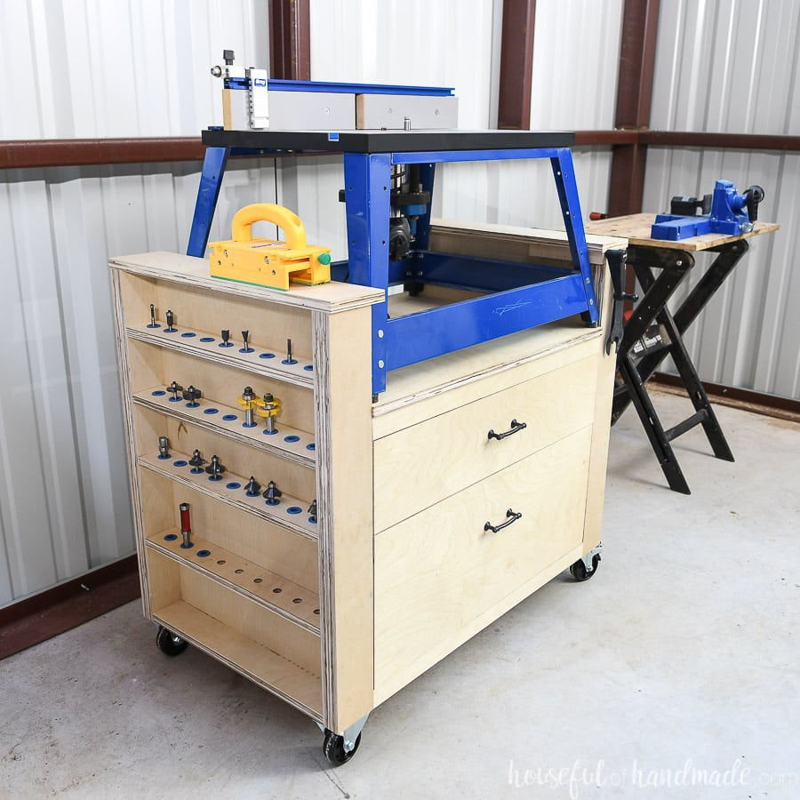 Angled shot of the DIY bench top router table made from plywood with a blue framed bench top router on it showing the side with the router bits storage.