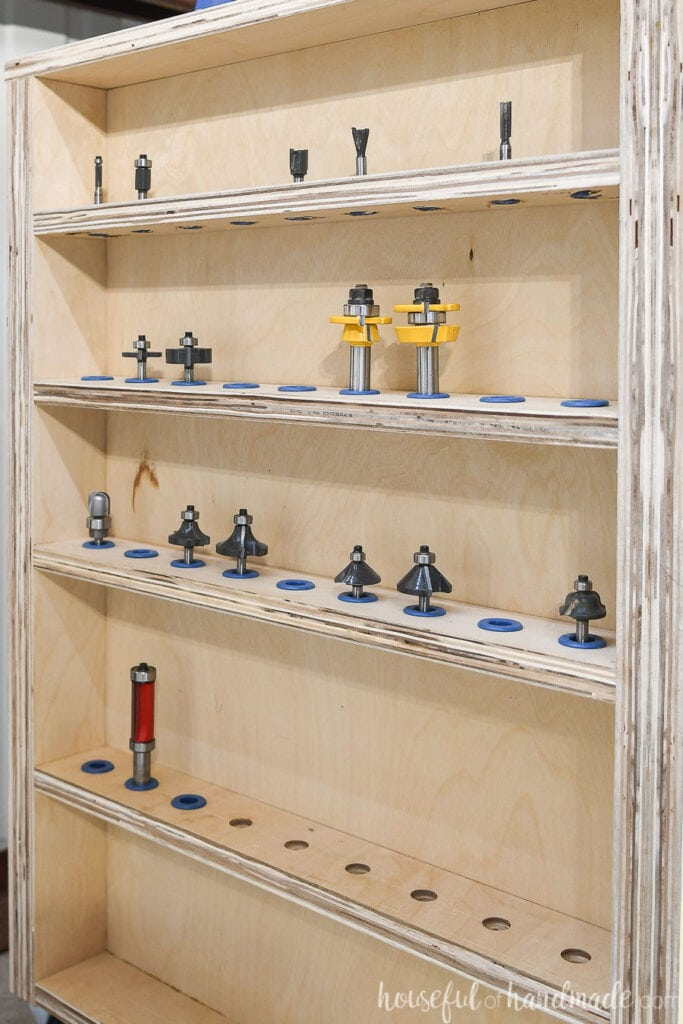 Close up shot of the router bit storage shelves on the side of the DIY router table with router bits installed in Rockler router bit inserts.