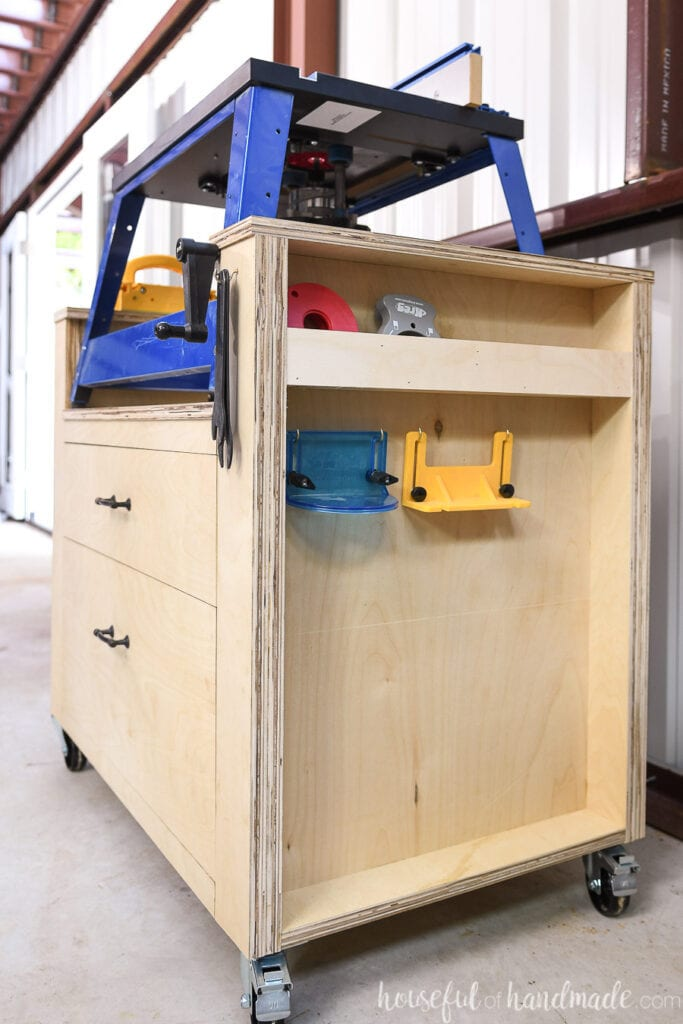 The right side of the router table made from plywood with cubbies and hooks for router accessories.
