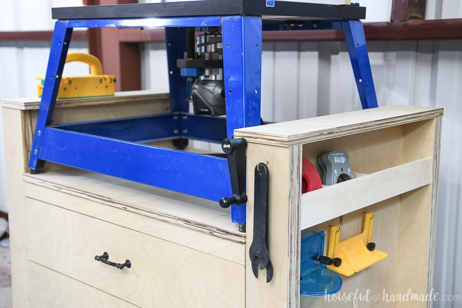 The right side of the router table with a spot under the raised side ledge holding the crank for the router lift and a hook holding the wrenches.