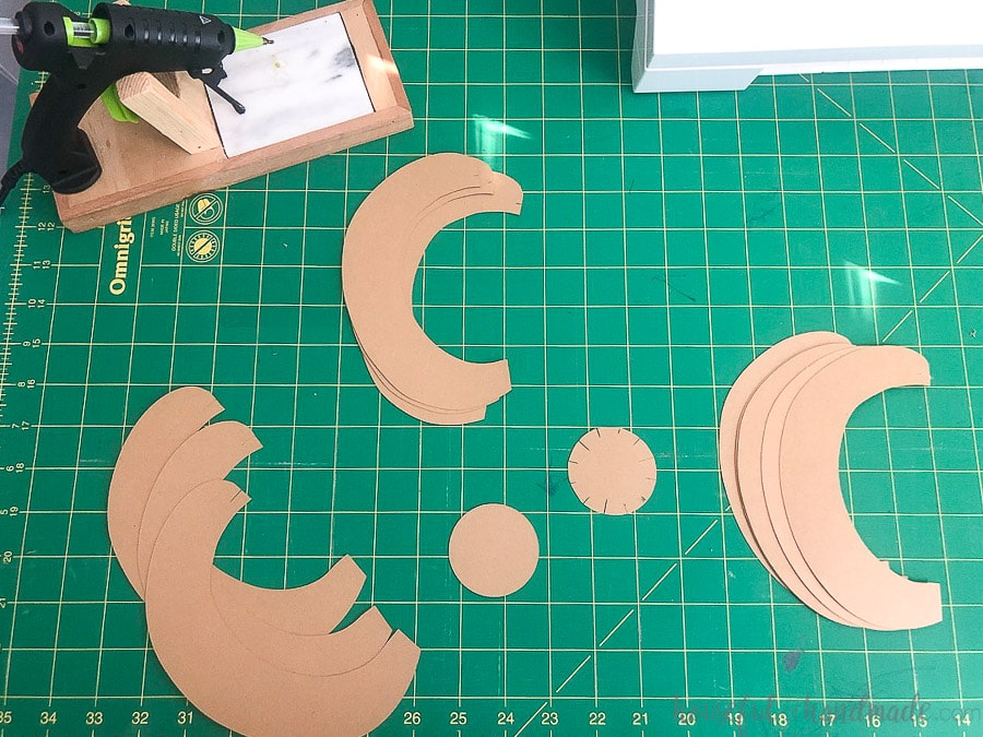 All the pieces of the 3d paper pumpkins cut out of brown craft paper laying on a green cutting mat.