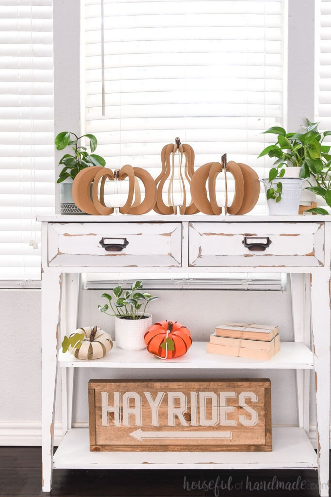 White farmhouse console table decorated for fall with 3D pumpkin lanterns, paper pumpkins, plants, books, and a wooden hayrides sign.