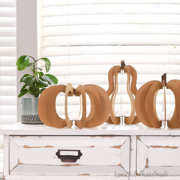 Three different shaped 3D paper pumpkins with tea lights inside them on a rustic console table with drawers.