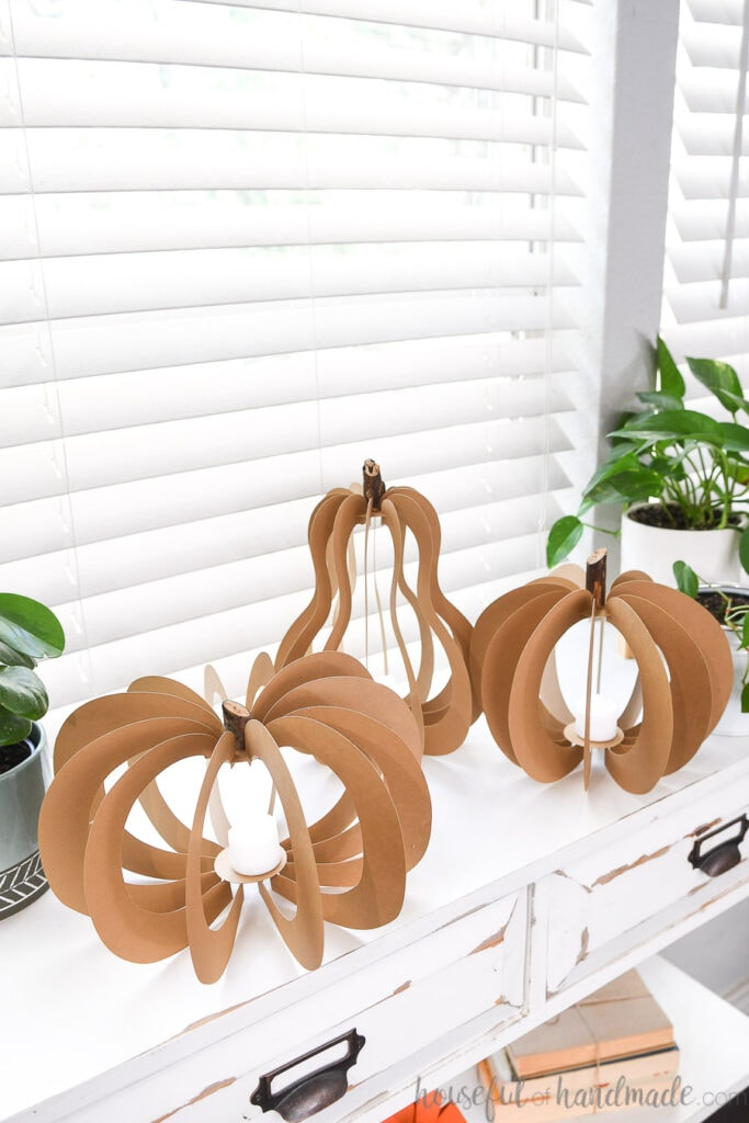 Pumpkin shaped paper lanterns made out of brown Kraft cardstock sitting on a white side table.