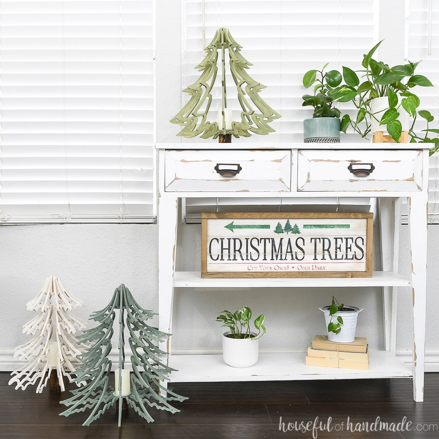 Three 3D wood Christmas tree lanterns sitting on and next to a small white console table.