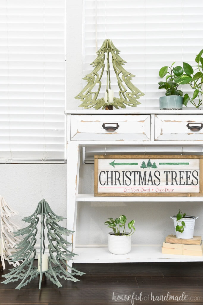 Christmas vignette on a white console table with 3D wood Christmas trees and a Christmas tree farm sign.