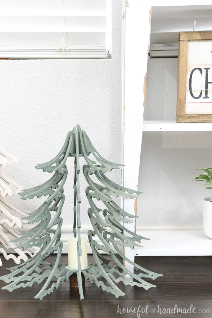 Close up of the Blue Spruce inspired wood Christmas tree lantern sitting on the floor by a white console table.