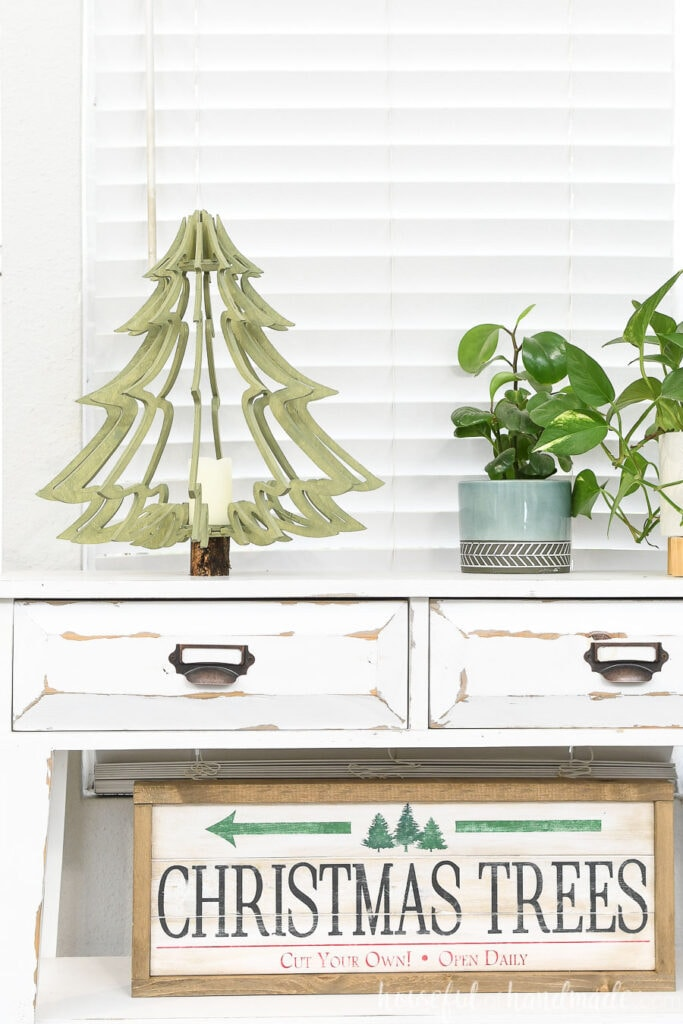 Large table top Christmas tree made from plywood on a console table next to house plants and above a Christmas tree wood sign.