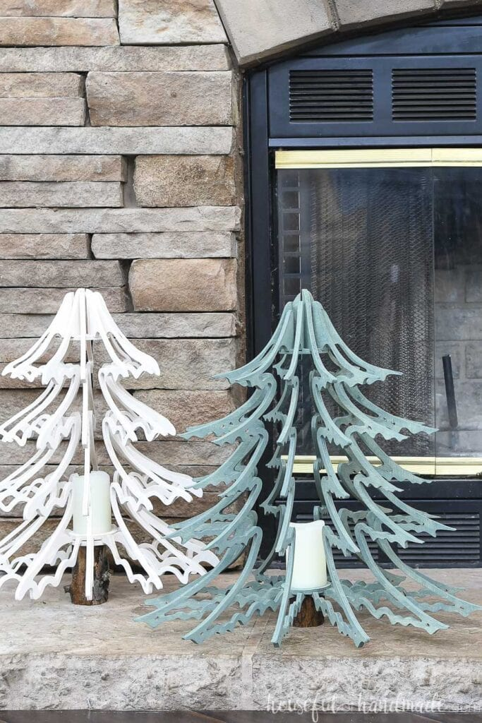 The white and blue-green stained plywood Christmas trees sitting on a stone hearth.