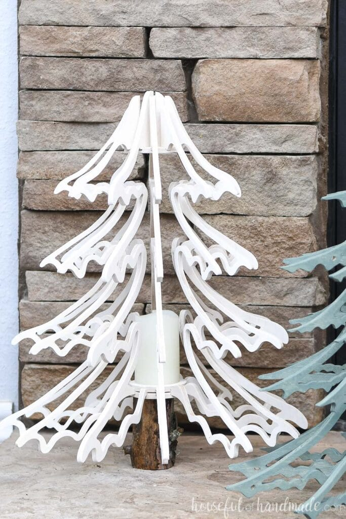 Close up of the smaller, white stained 3D wood Christmas tree with drooping branches sitting on the hearth.
