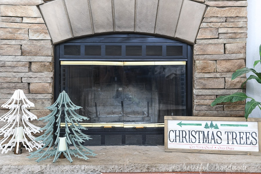 Two 3D wood Christmas tree lanterns sitting on a stone fireplace hearth with a Christmas tree farm sign on the other side of the hearth.
