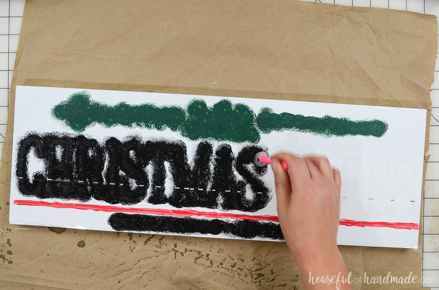 Stippling black, red and green craft paint over the Christmas tree vinyl stencil.