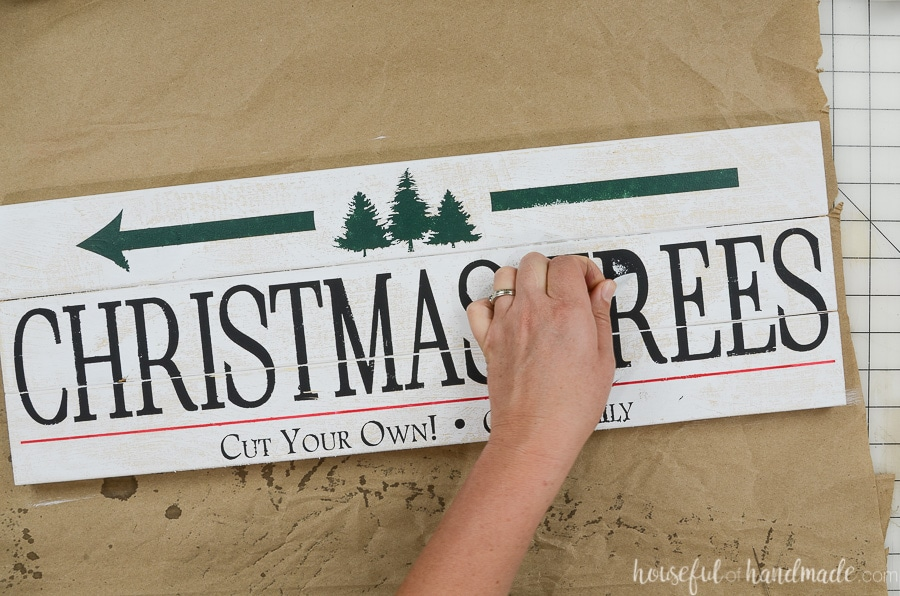 Peeling off the last of the vinyl stencil revealing the Christmas tree farm sign.