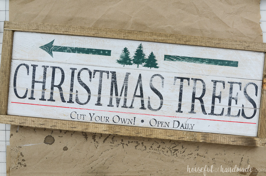 The completed Christmas side of the double sided sign laying on top of a piece of brown paper on a work table.