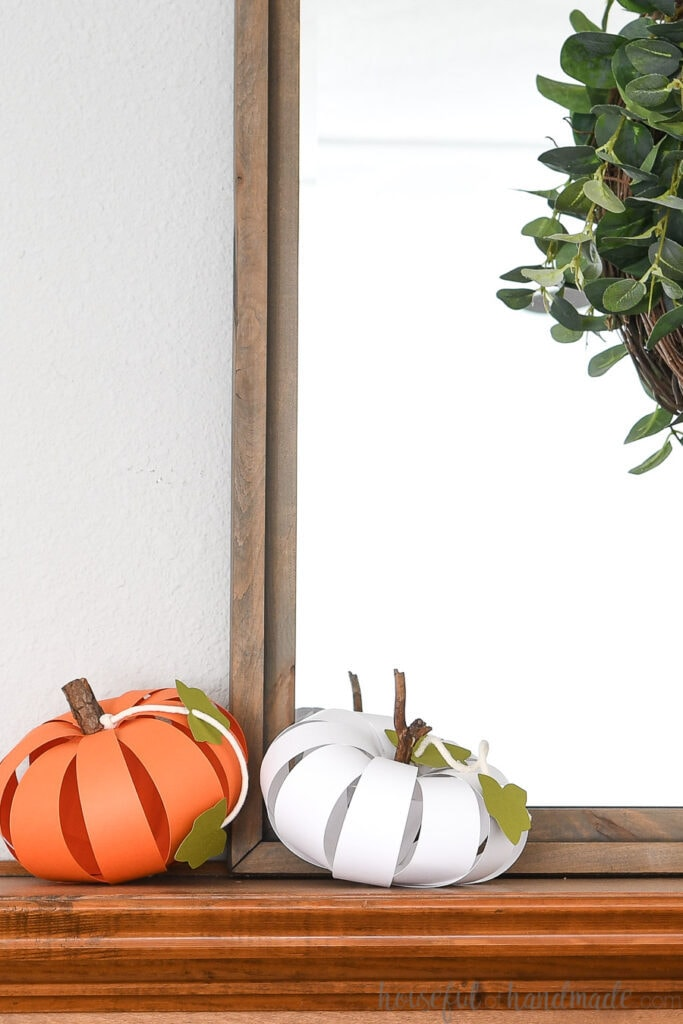 White and orange paper pumpkins on the mantel in front of a gray framed mirror.