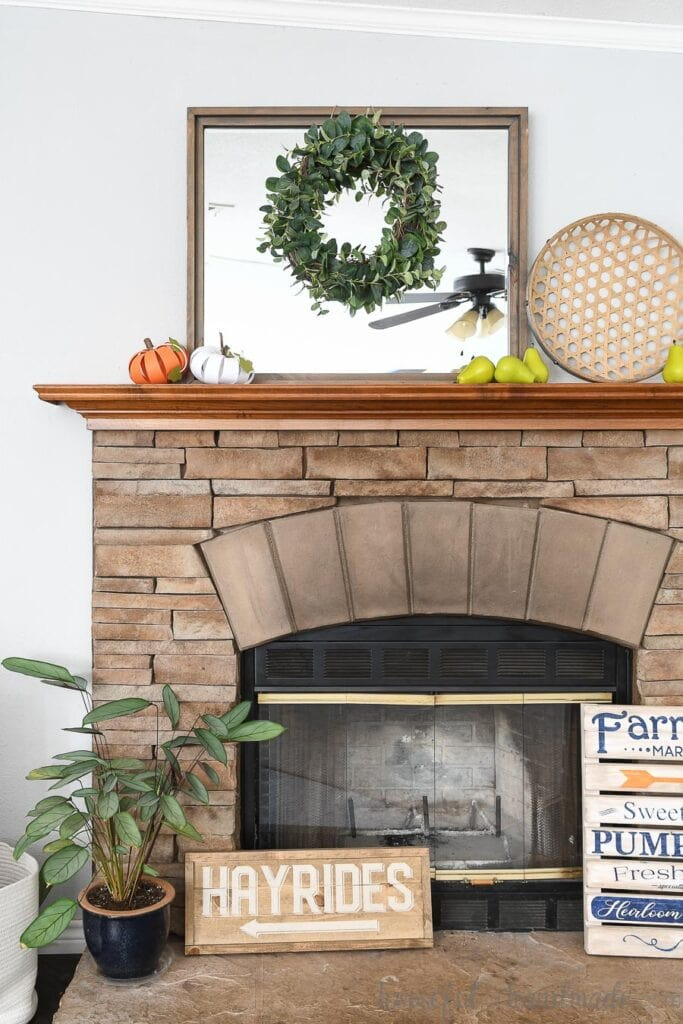 Stone fireplace with wood mantel decorated for fall with wood signs, a mirror, and paper pumpkins.