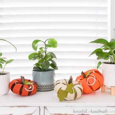 Three colorful paper pumpkins with sticks for stems on a console table.