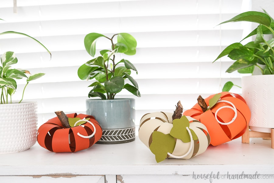 Three different sized pumpkins made from cardstock on a table next to house plants.