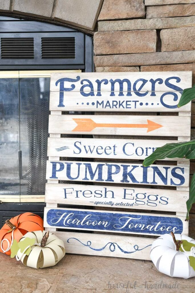 Farmers Market pallet sign on the fireplace hearth with 3 DIY paper pumpkins on the hearth in front of it.