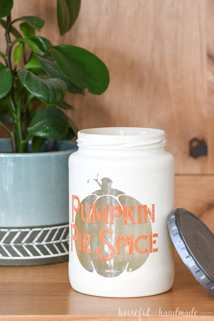 Close up of the Pumpkin pie spice kitchen canister with the lid off leaning up against the side.