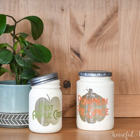 Two fall themed kitchen canisters in a wood hutch with a houseplant in the background.