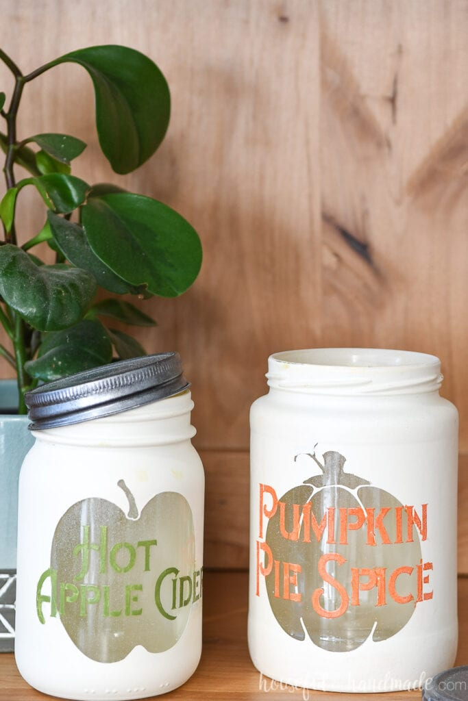 Close up of the two completed fall kitchen canisters, one with a pumpkin shape and the words pumpkin pie spice on it and the other with and apple shape and the words hot apple cider on it.