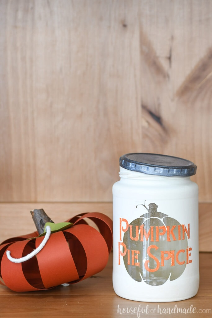 Close up of the Pumpkin Pie Spice kitchen canister next to a paper pumpkin craft.