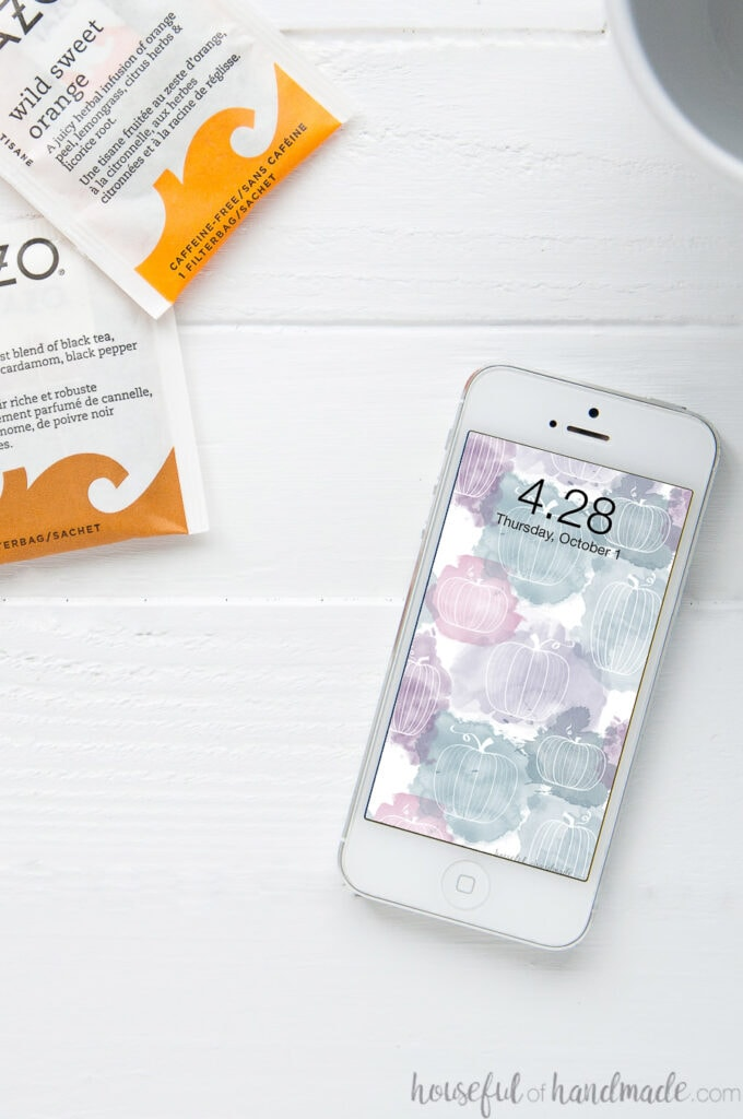 White iPhone on a white table next to fall tea pouches with the free digital wallpaper for October on the home screen.