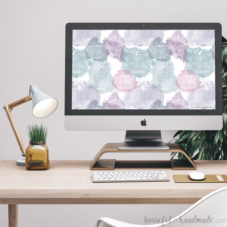 Computer showing the purple & teal pumpkin design wallpaper on a desk with a lamp and plant.