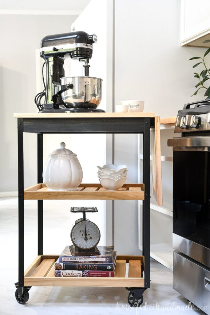 Black and wood modern rolling kitchen cart with stand mixer on top next to a stove.