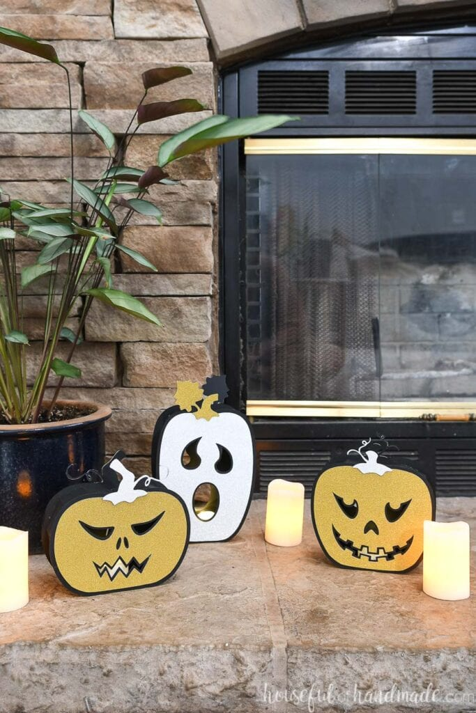 Two standard jack-o-lantern faced and one ghost faced paper jack-o-lanterns on the hearth with candles next to them.