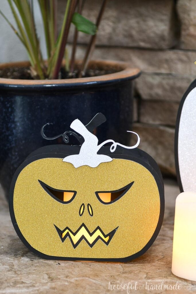 Close up of the short paper jack-o-lantern on the hearth with a candle inside.