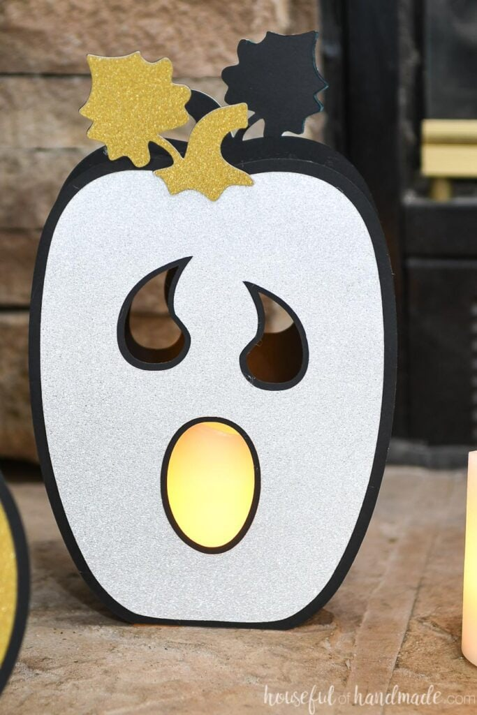 Close up of the ghost faced tall pumpkin lantern with silver glitter cardstock pumpkin face.