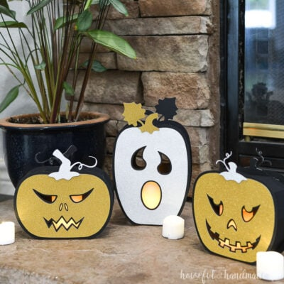 Three Jack-O-Lantern shaped halloween lanterns made from paper, two with gold faces and one with silver.