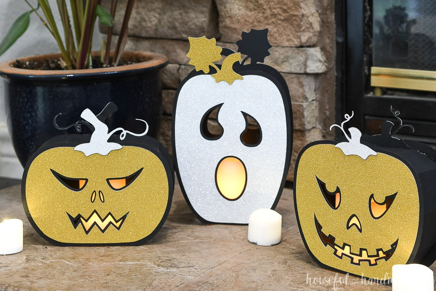 Three Halloween paper lanterns that look like jack-o-lanterns with flameless candles inside.