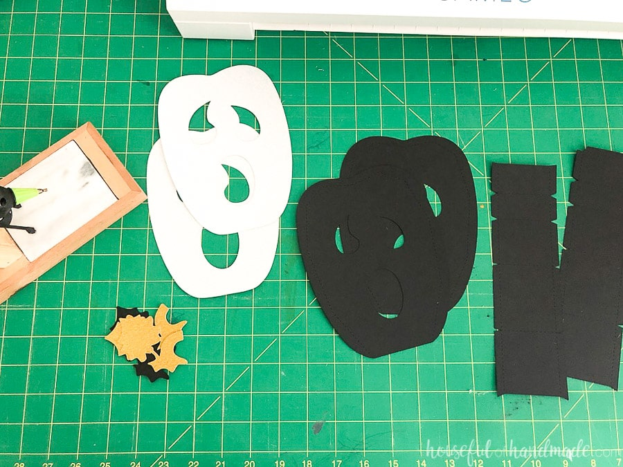 Ten pieces for the tall ghost face paper jack-o-lantern cut out of cardstock sitting on a green cutting mat.