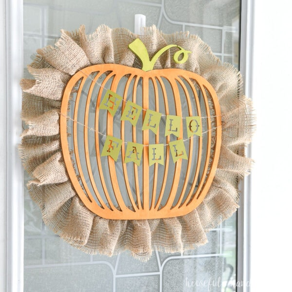 "Door with a window on it and a wood pumpkin wreath with a ""Hello Fall"" paper banner on it."
