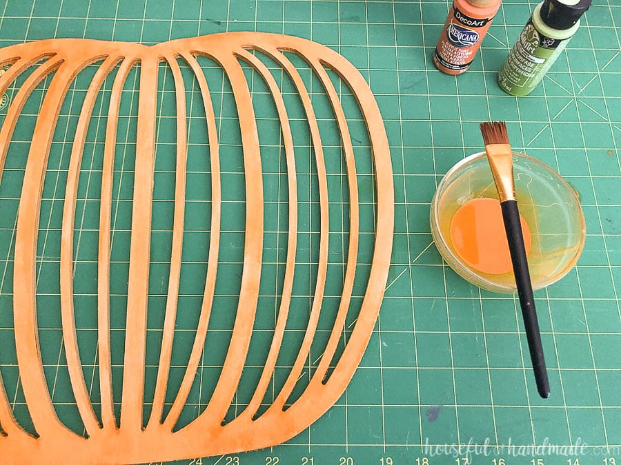 Plywood pumpkin shape painted with a watered down orange paint mixture.