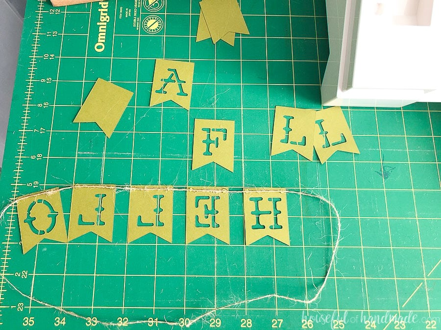 Letters for the Hello Fall banner cut out of the banner pieces and laid on the cutting mat upside down and backwards with the string glued to them.
