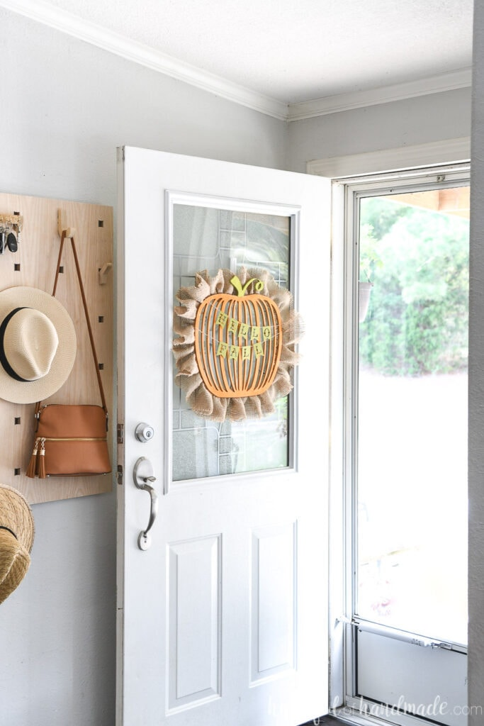 Entryway with door to the outside open and a wood pumpkin wreath hanging on it.