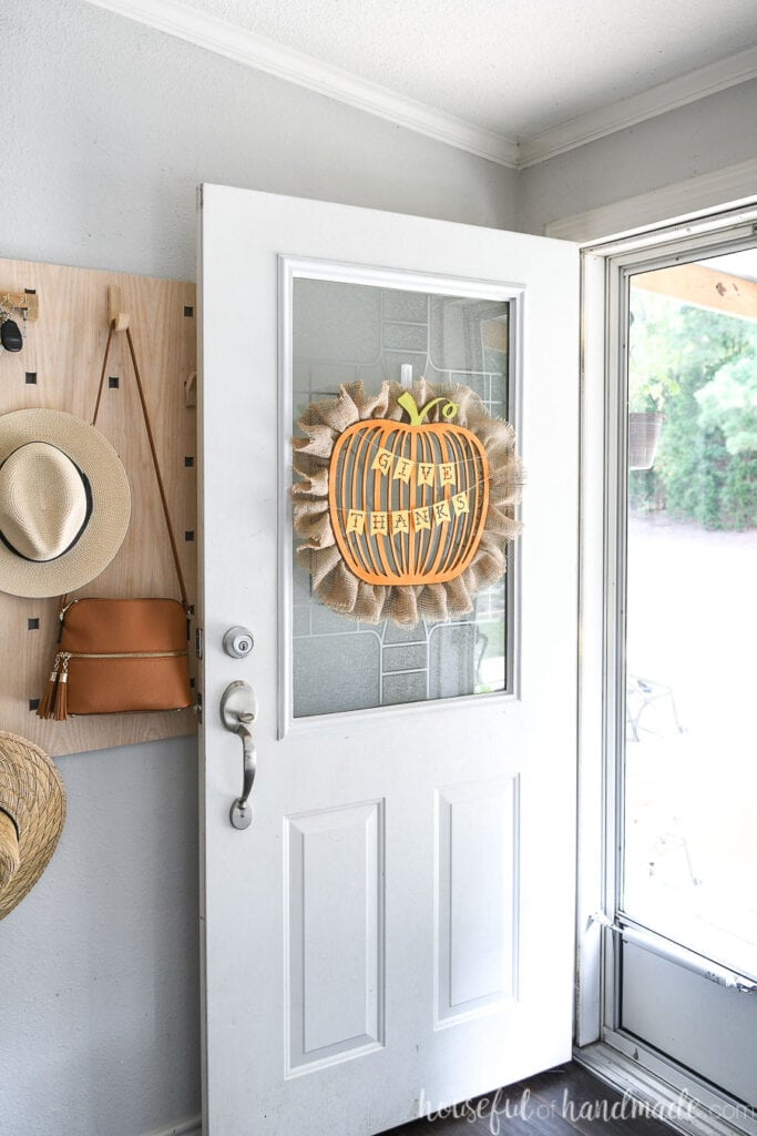 White door with modern pumpkin wreath with words Give Thanks on it.
